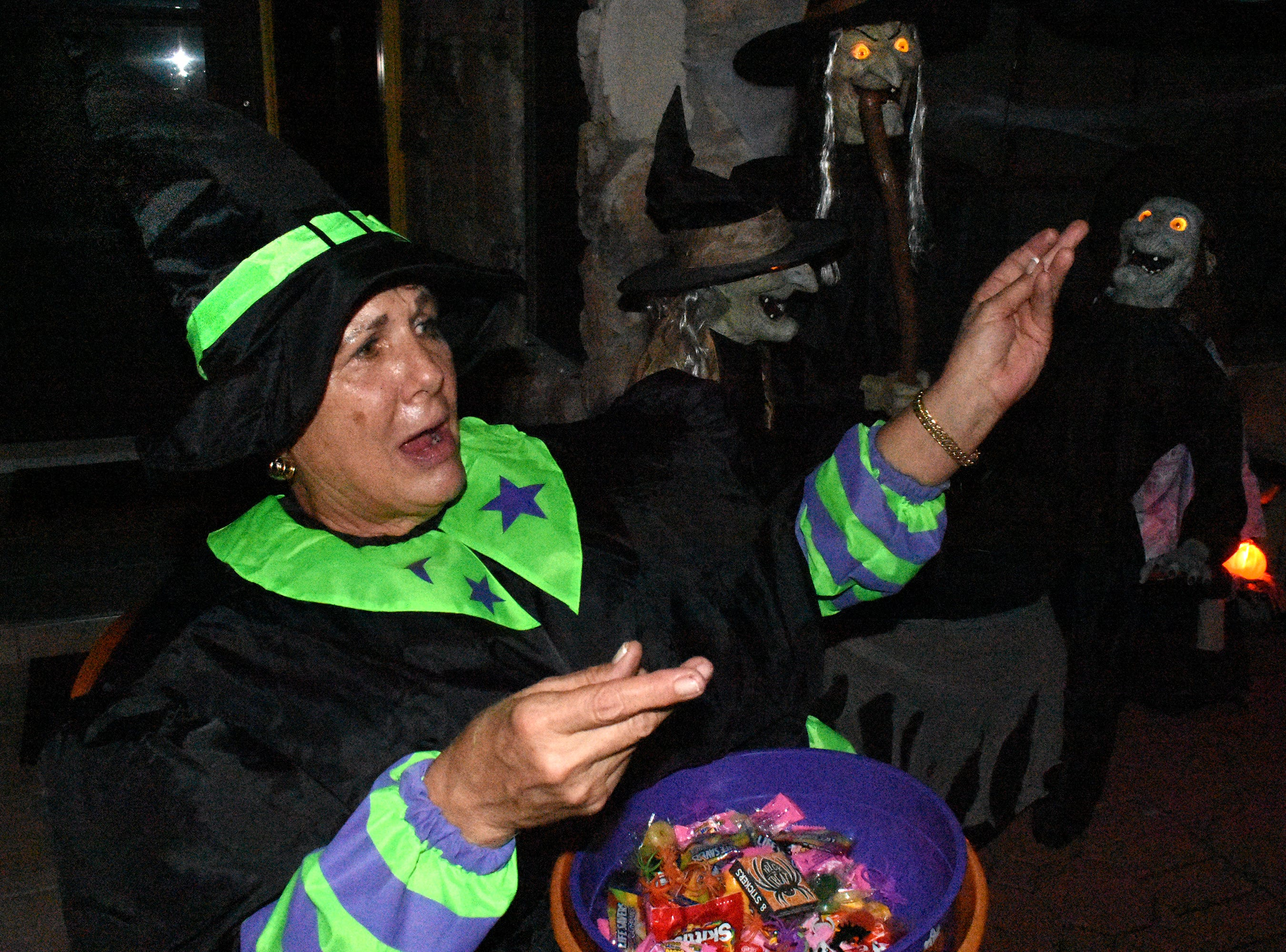 Bonnie Woodward hands out candy surrounded by other witches. Wednesday evening, in a decades-old tradition, the streets around Tommie Barfield Elementary turned into a trick or treatin' block party.