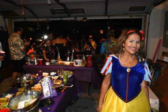Eymy Griska, decked out as Snow White, puts out a buffet in her garage. Wednesday evening, in a decades-old tradition, the streets around Tommie Barfield Elementary turned into a trick or treatin' block party.