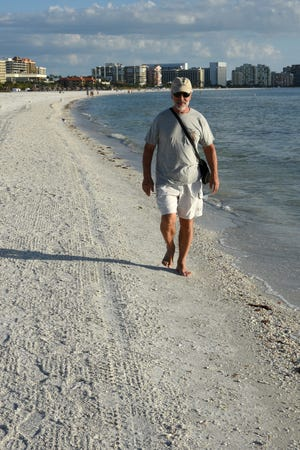 NIkolai Kubay walks the water's edge at Residents Beach. Beach work will stop just north of the Marriott hotel. Collier County will begin a million dollar-plus reshaping of the beach along Marco Island in the early months of 2019.