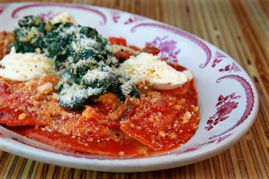Mezzaluna, half-moon pasta filled with braised pork and mascarpone, are served in spicy tomato sauce and topped with spinach and garlic breadcrumbs at Brandywine.