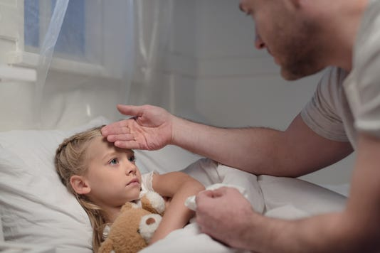 Father Touching Forehead Of Sick Daughter