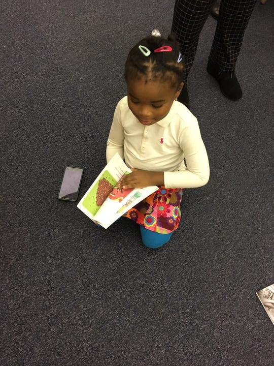 Yona Deacon, 4, reads while she waits for her mother after a news conference announcing a new citywide early childhood education initiative Thursday at Gwen T. Jackson Early Childhood and Elementary School.