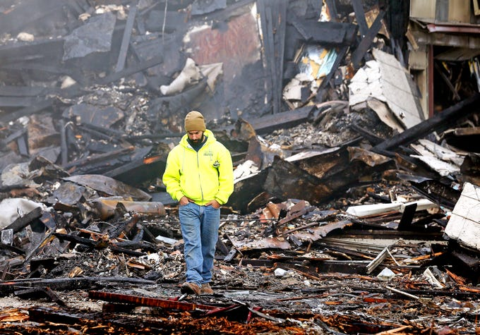 A contractor walk among the ruins in the aftermath of a devastating fire on North Warren Street in Dover that collapsed multiple businesses in a fast-moving, seven-alarm blaze that officials say started in the basement of Barry's restaurant. The fire then spread throughout the building and to others nearby that contained businesses and apartments Displacing about 100 people from their homes. October 23, 2018, Dover, NJ