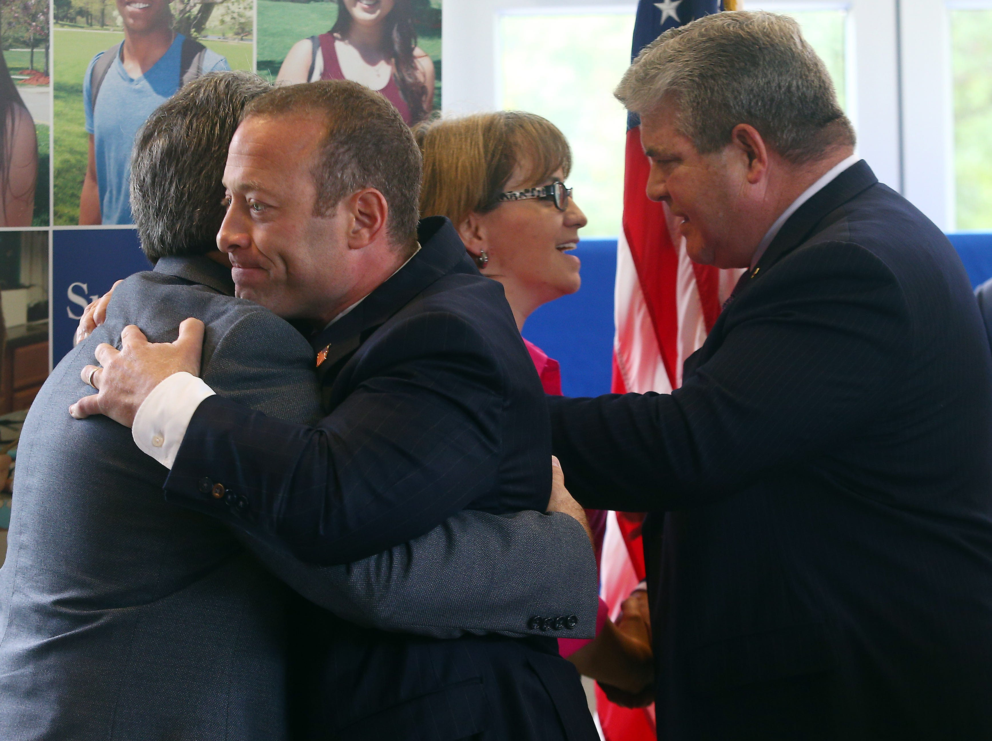 Congressman Josh Gottheimer hugs Adam Stolarsky as Colleen Murch shakes hands with  Senator Steven Oroho after the Stand United Against Hate rally at the Performing Arts Center of Sussex County Community College. Hampton Township residents Murch and Stolarsky found vulgar graffiti sprayed on the road in front of their residence. This followed an incident last weekend in which a vandal spray-painted a swastika on their garage and a campaign sign for Rep. Josh Gottheimer. October 2, 2018, Newton, NJ