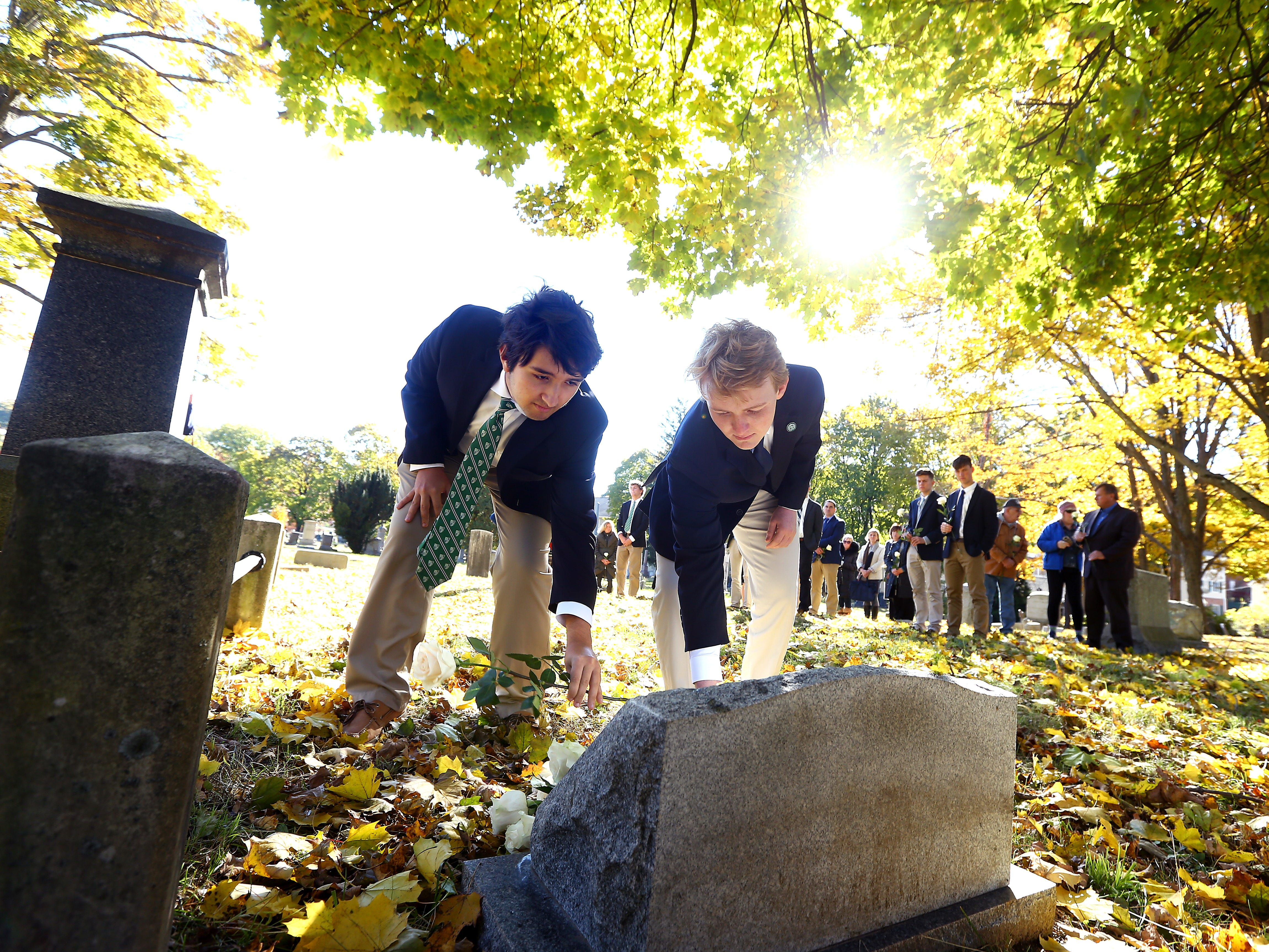 Delbarton students place roses after a graveside service and blessing at Orchard Street Cemetery in Dover, gathering to bless the grave for baby Anthony Mary, whom they so-named after he was abandoned and found deceased at a recycling center in Mine Hill. October 30, 2018, Dover, NJ