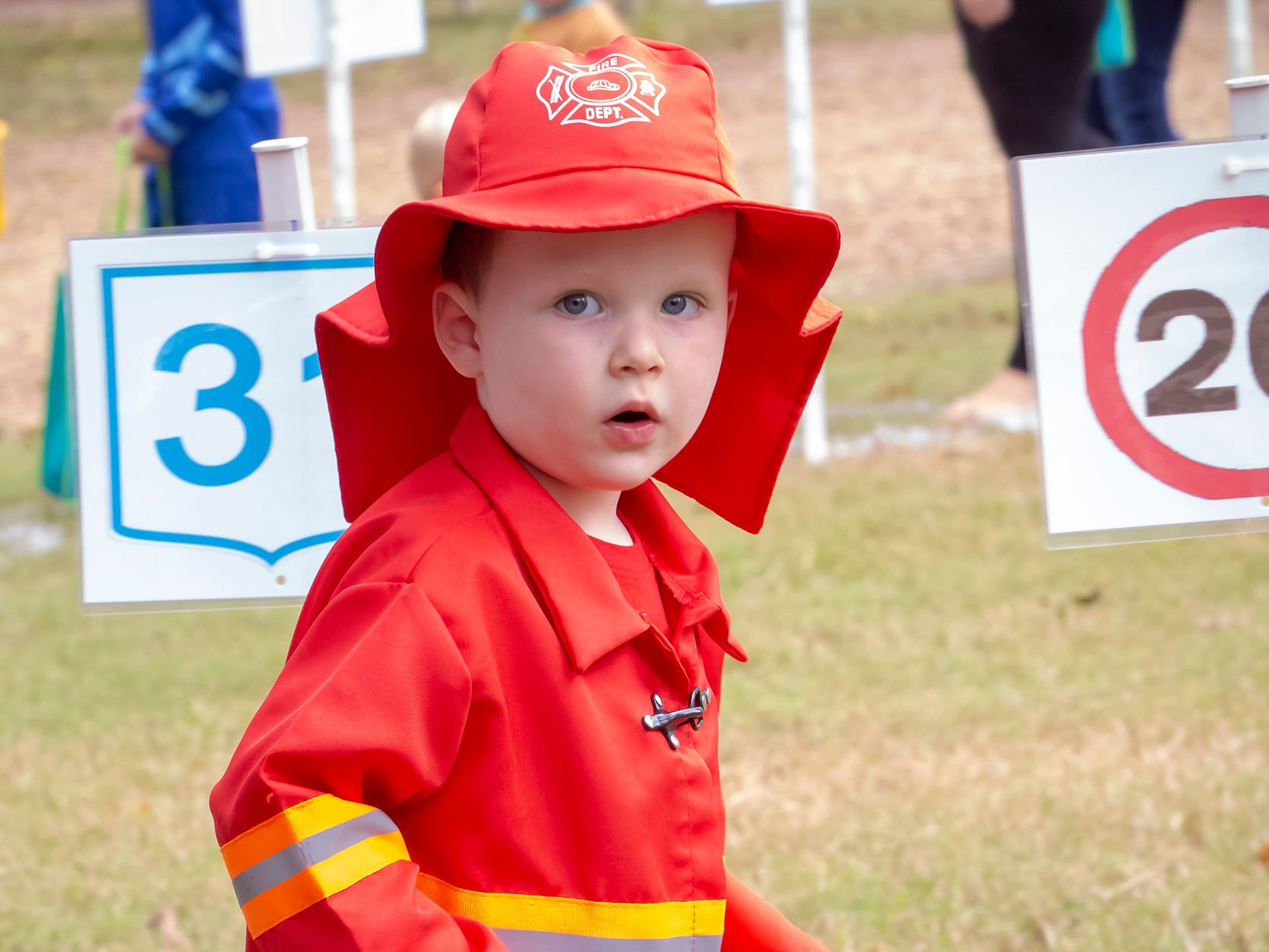 Bennett Schuster, dressed as a Firefighter, takes a step in the Book Walk, aka the Cake Walk, at the Fall Celebration and Hayride at Cannonsburgh Village.