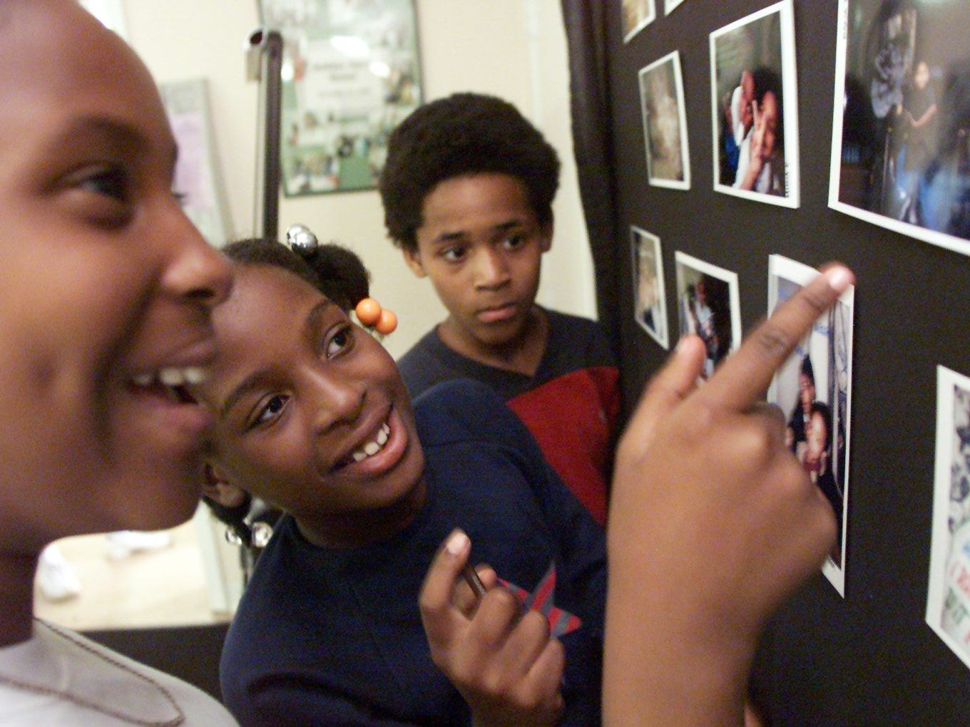 Ilham Eli, 11, left, Dana Fields, 9, and Devion White, 10, look at some of their photos displayed at the Cayce Learning Center on May 15, 2002.