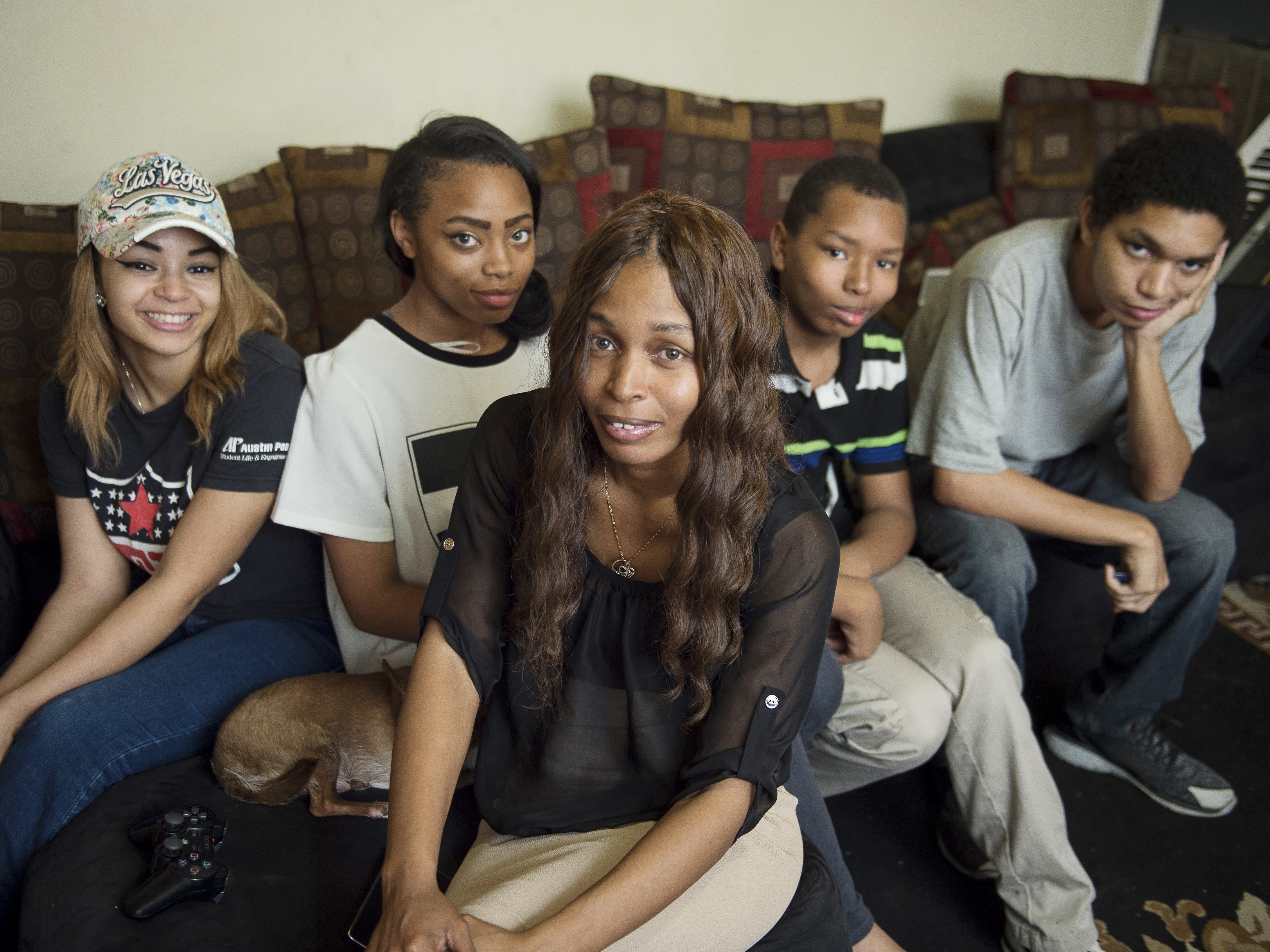LaConya Hampton, front, and her children, Tatiana Parham, 17; Treasure Hampton, 15; Stanly Boyd, 12; and Timothy Parham, 19, are in their apartment at the James A. Cayce Homes on March 21, 2017. They are looking forward to moving to a new home in a Habitat for Humanity community.