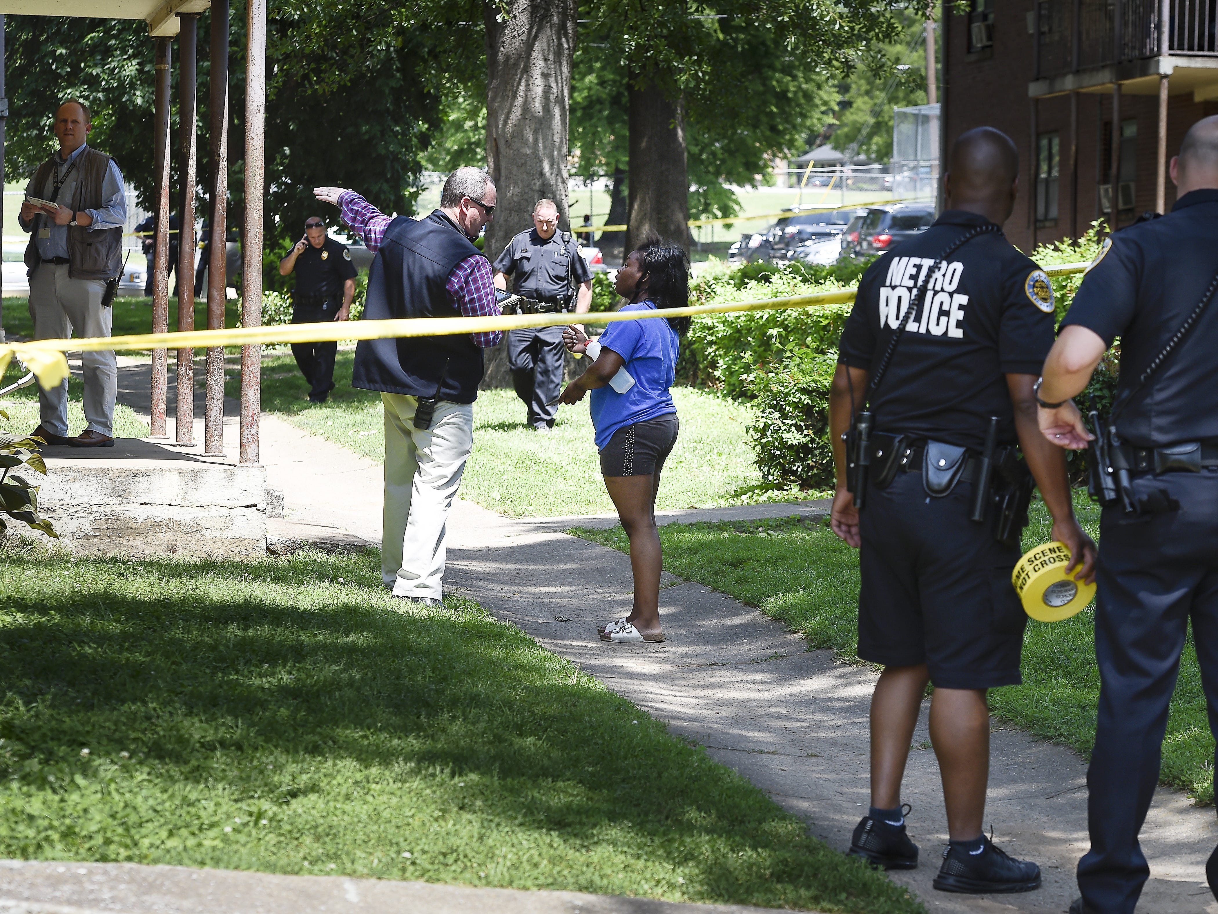 Metro police officers investigate a shooting in which one man was killed and two others were wounded on South Eighth Street in the James A. Cayce Homes on May 19, 2017.