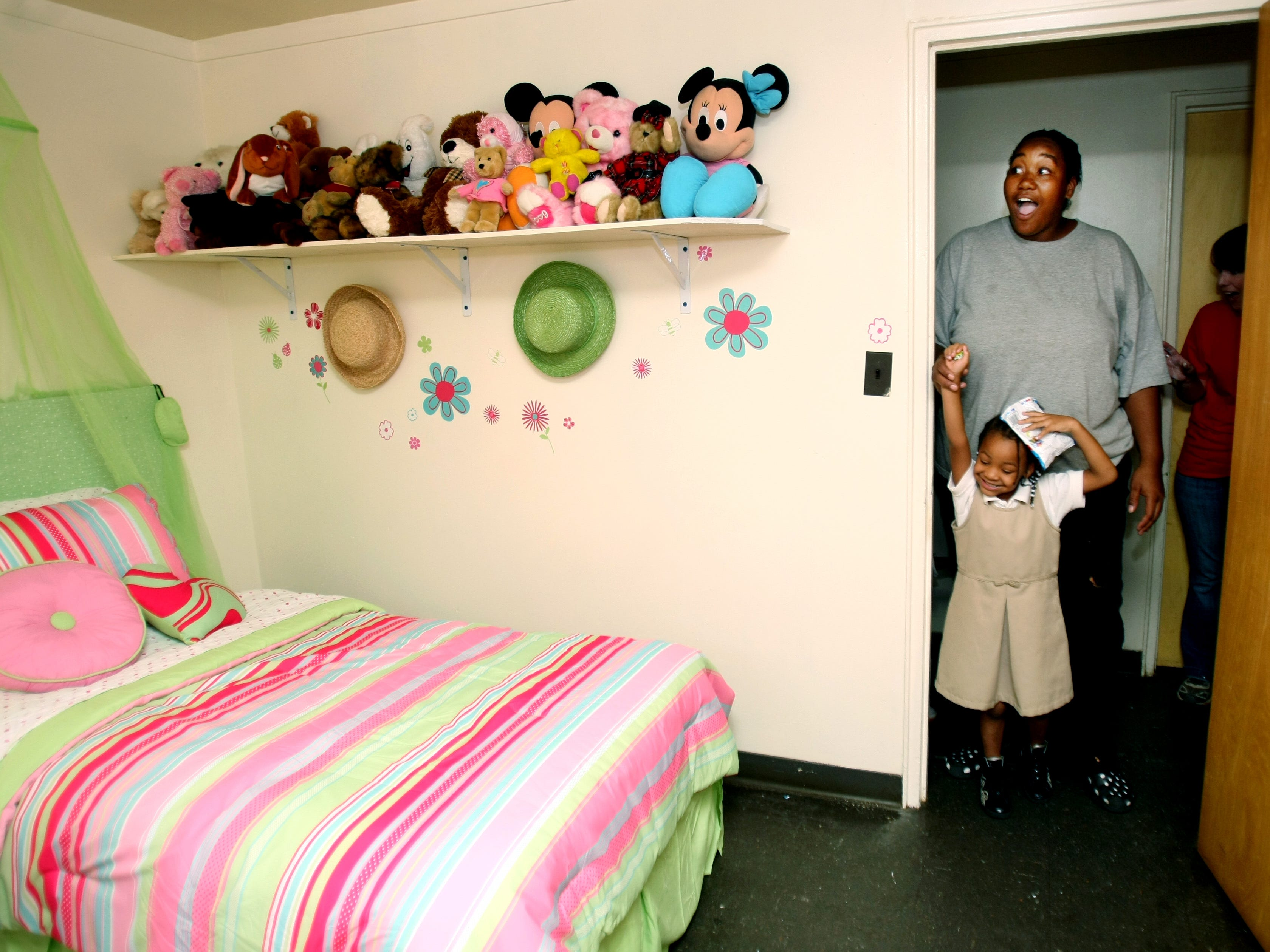 James A. Cayce Homes resident Tara Malone, 27, and her daughter Zena Malone, 4, walk into Zena's newly designed  bedroom for the first time Sept. 26, 2009. The room was redesigned by Project Redesign, a program that provides furniture for families in immediate crisis and redesigns rooms for needy families.