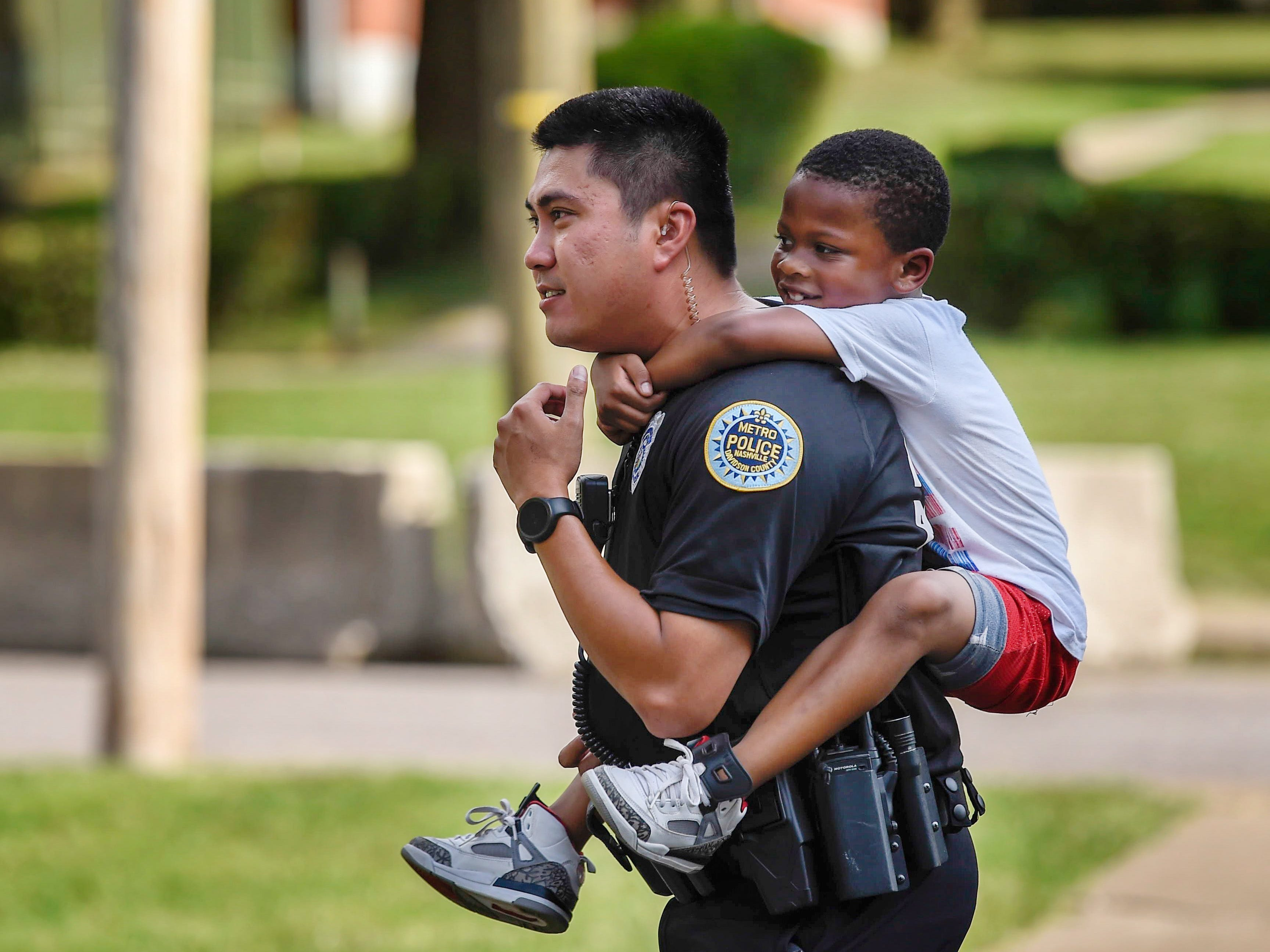 Metro Nashville Police Department Officer Ky Luu carries Denzel Bigham, 7, on his shoulders back to his home in the James A. Cayce Homes housing development Aug. 30, 2018.