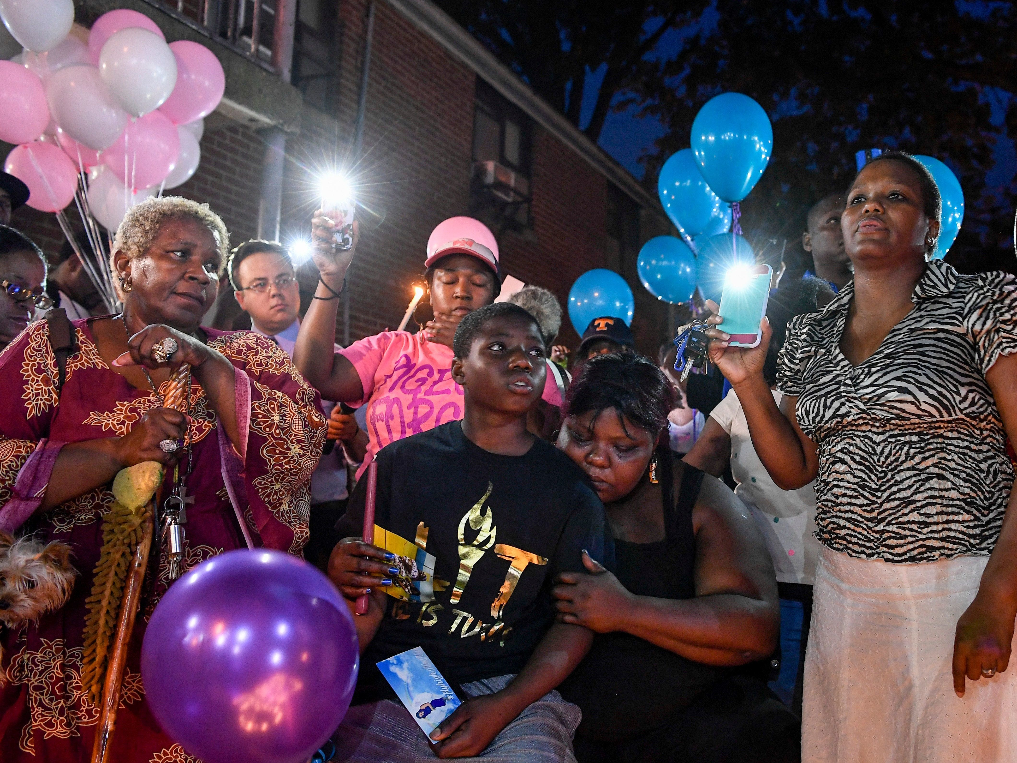 Deberianah Begley's brother Danquan and mother, Tika Begley, are surrounded by friends and family during a candlelight vigil Oct. 9, 2017, at the James A. Cayce Homes.