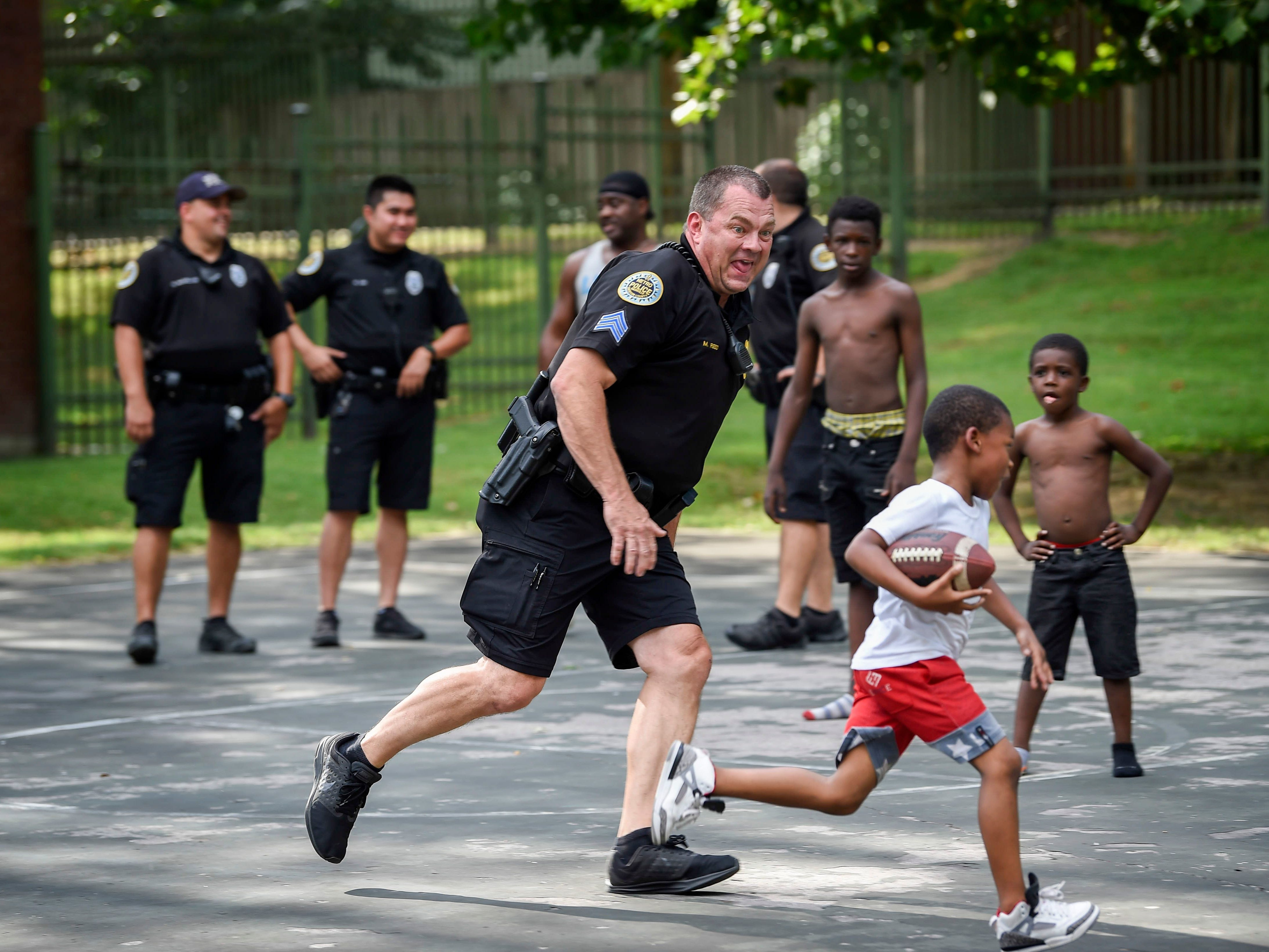 Sgt. Marty Reed with the Metro Nashville Police Department chases Denzel Bigham, 7, as the officers play football with the neighborhood children in the James A. Cayce Homes housing development Aug. 30, 2018.