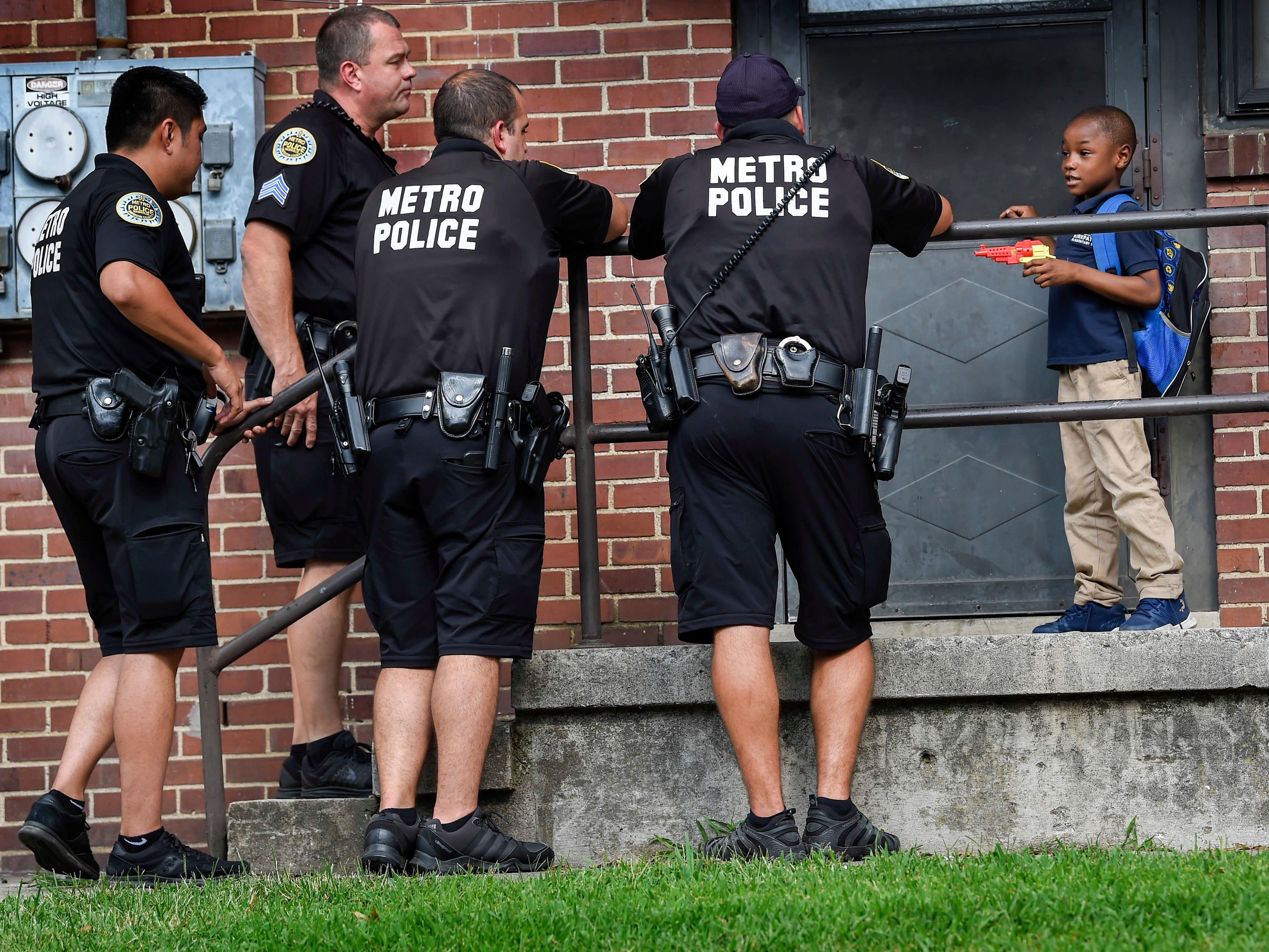 Officers with the Metro Nashville Police Department stop to talk with Marqual Goins, 7, as they walk through the James A. Cayce Homes housing development to help establish relationships with residents Aug. 30, 2018.