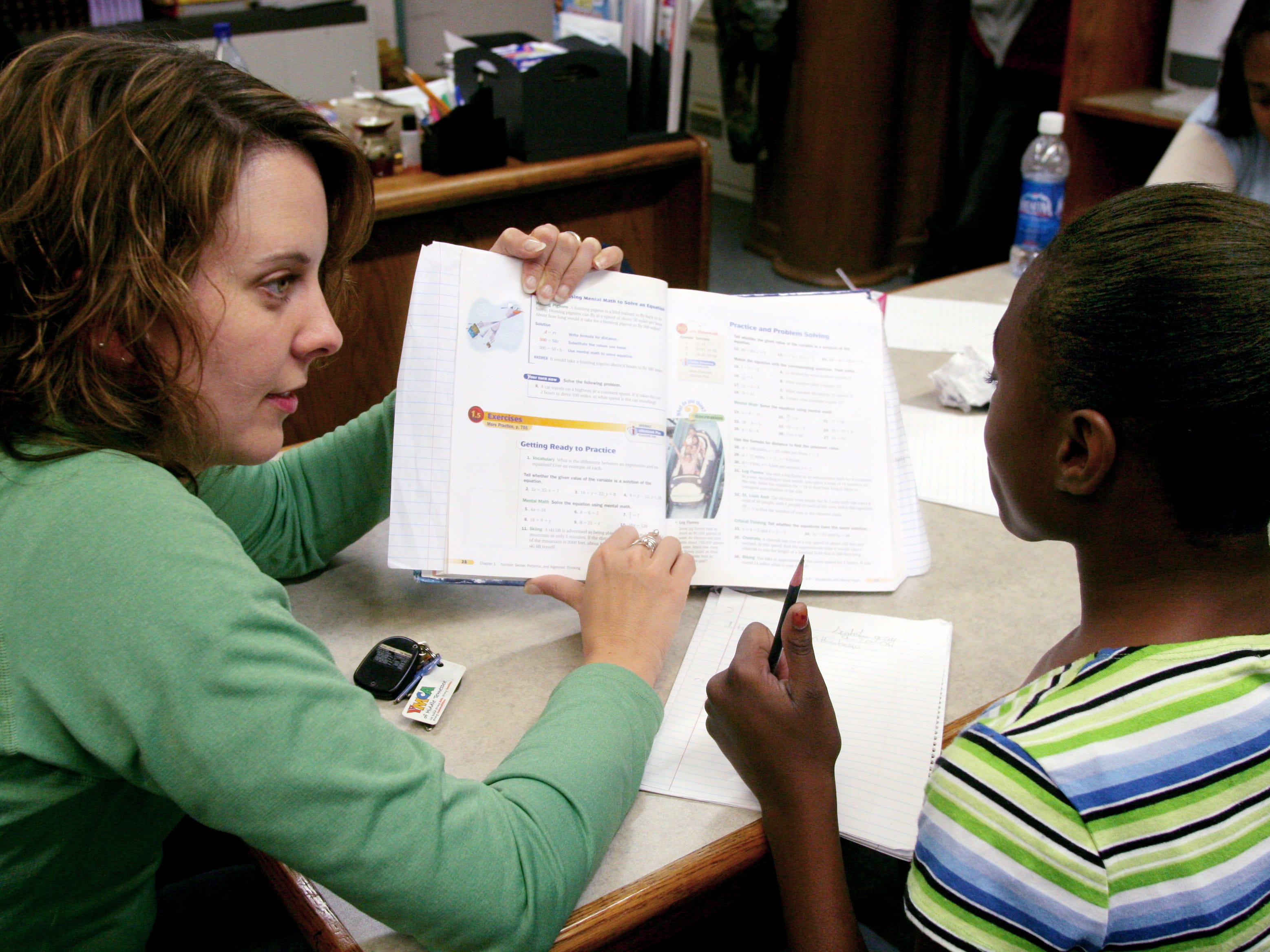 """Jennifer Fouse, campus Presbyterian minister at Vanderbilt University, helps Dalewood Middle School student Scotisha Gray, 13, with her math homework during """"Plus Time"""" at the Cayce Family Resource Center inside the Martha O'Bryan Center on Sept. 20, 2006."""