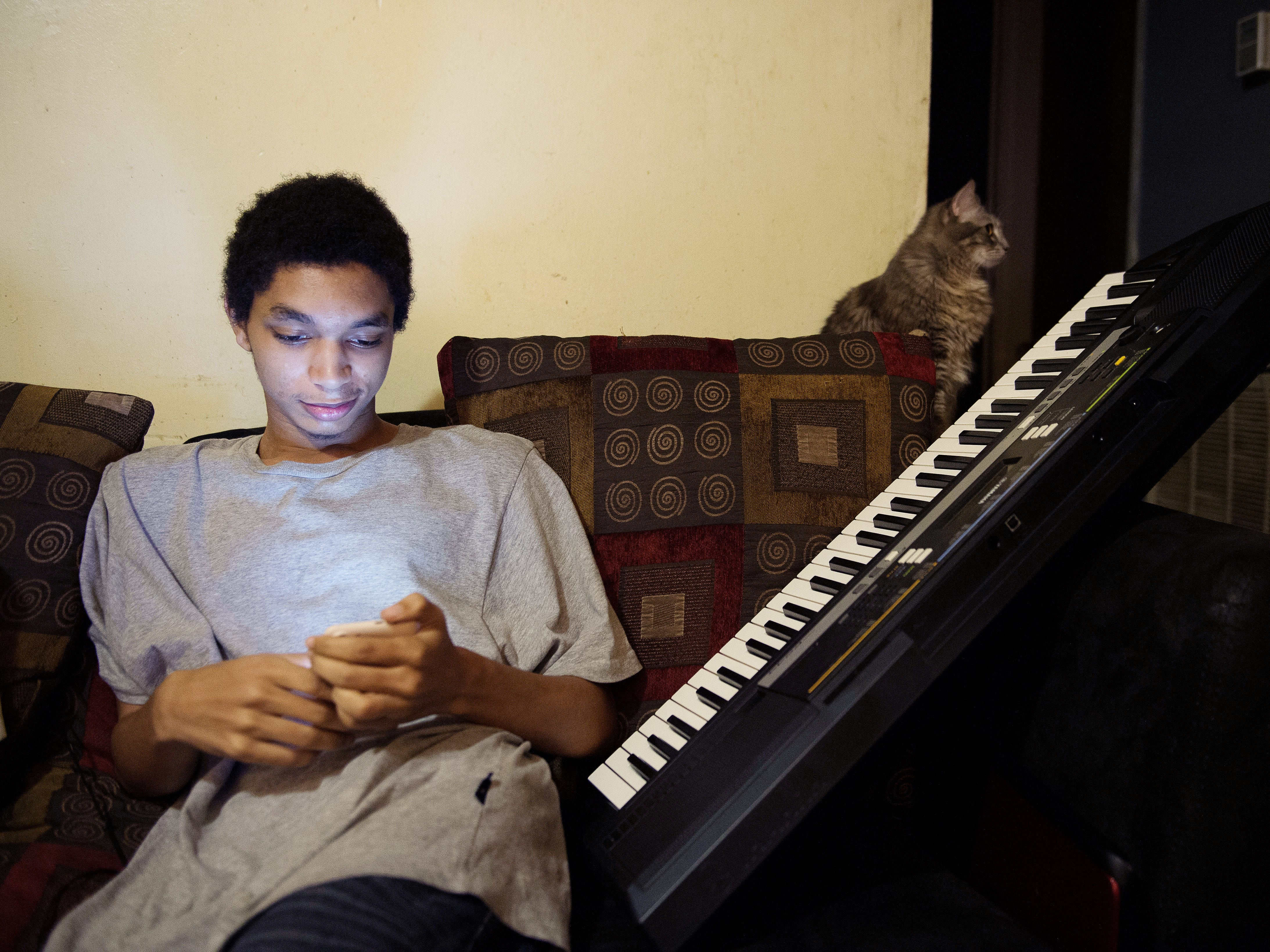 Timothy Parham, 19, son of LaConya Hampton, checks out his phone as he enjoys an evening at their apartment in James A. Cayce Homes on March 21, 2017.