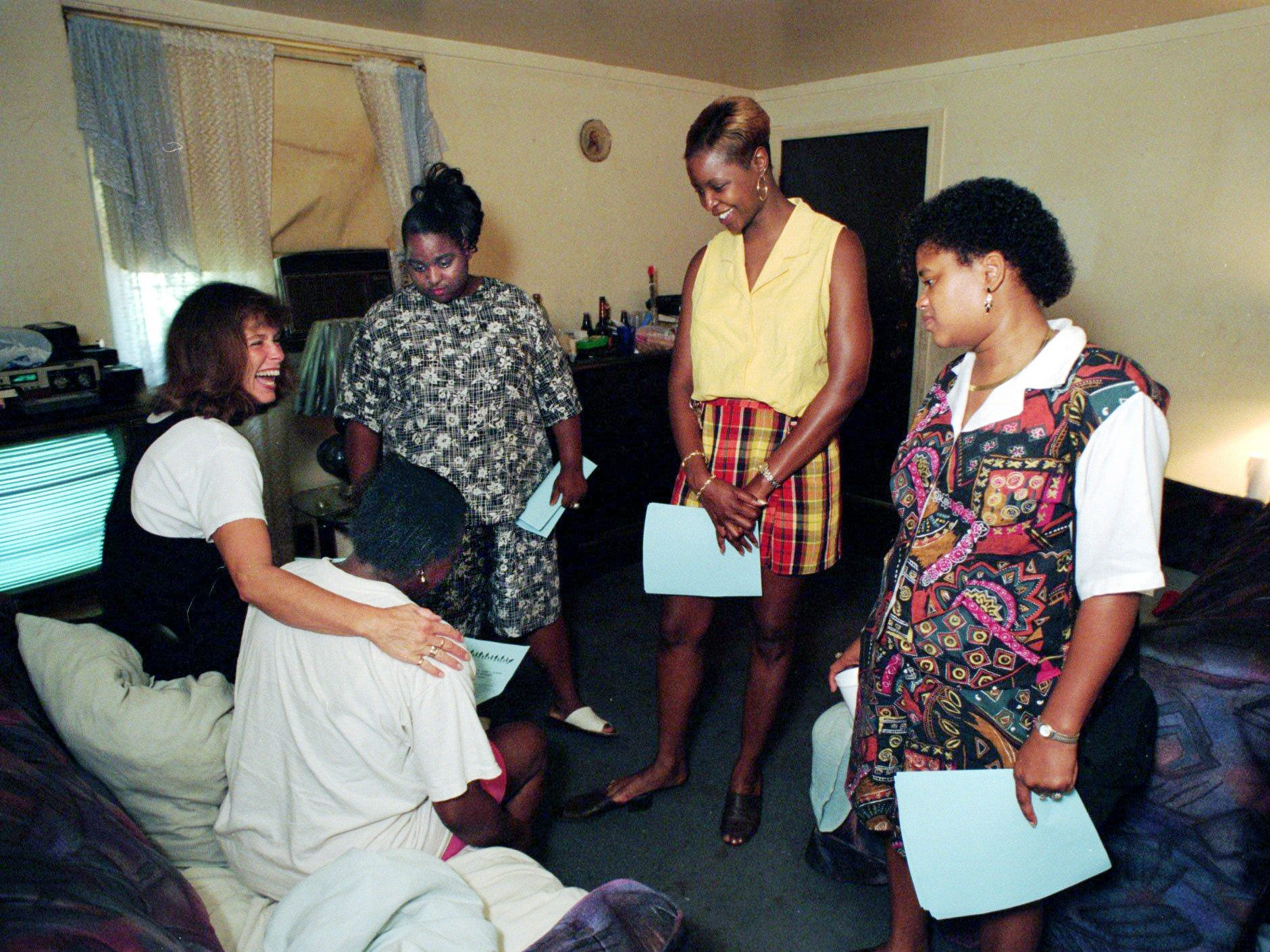 Parent recruiters from the East Nashville Center for Family, School and Community Partnerships visit Janette Newsom, seated, in the James A. Cayce Homes on Aug. 30, 1996. They are center director Sujette Overstreet, Crystal Beverly, Tracy Thomas and Ann Braden.