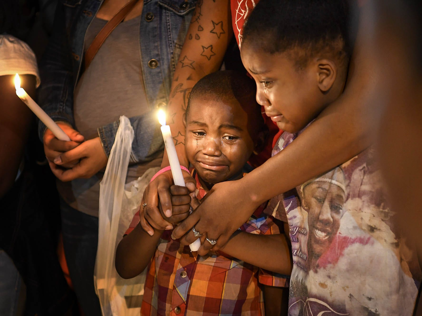 Latrelle Cox Jr. and Corionna Offutt are held by their mother as they pay their respects for Deberianah Begley during a candlelight vigil at the James A. Cayce Homes on Oct. 9, 2017.