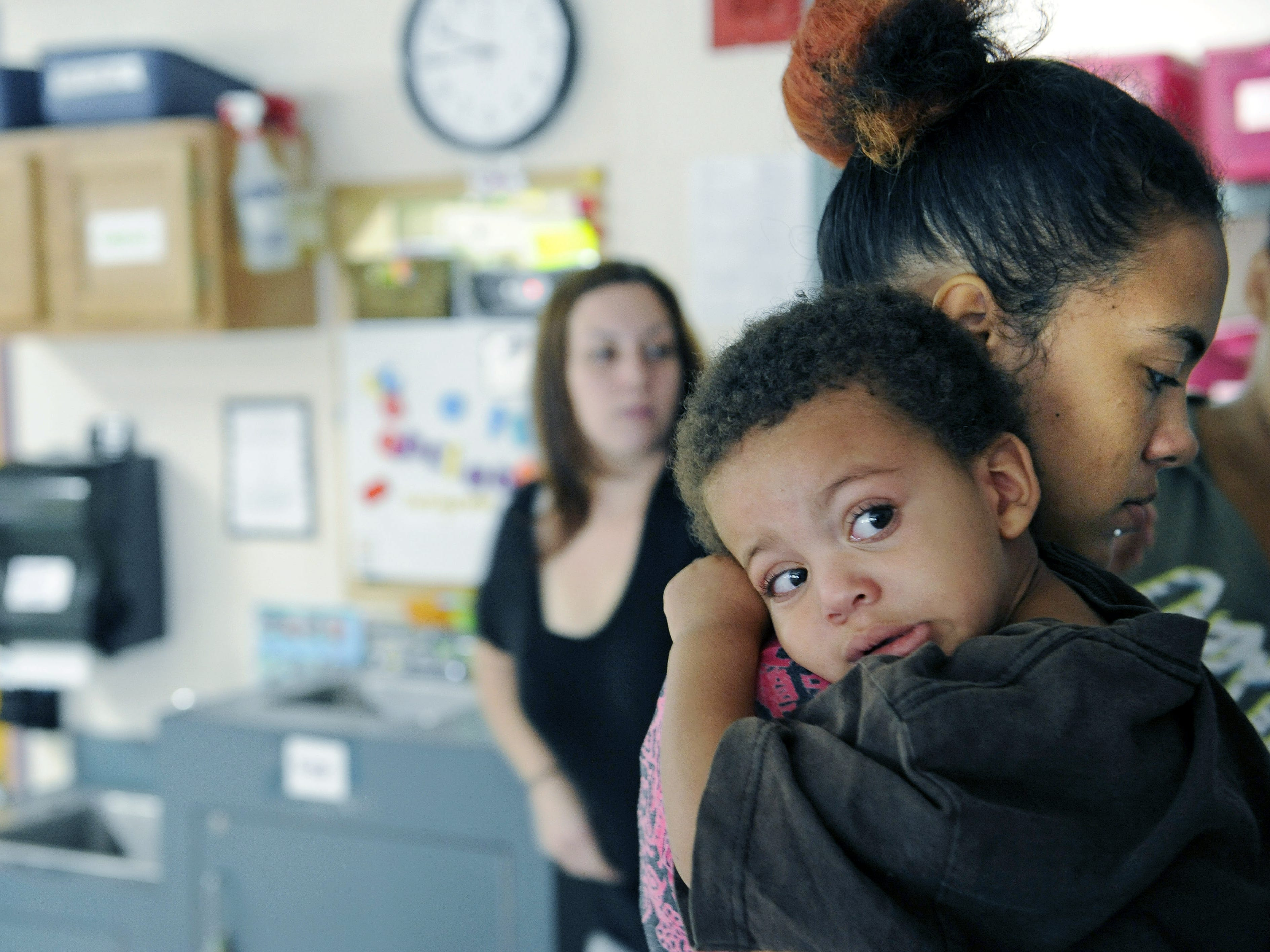"""Satarah Sauls, 23, holds her 2-year-old son, Nolan, as she brings him into the day care at the Martha O'Bryan Center before class Aug. 18, 2012. Sauls has lived in James A. Cayce Homes for about six months and says the Tied Together class taught her to commit to being her son's """"first teacher."""""""