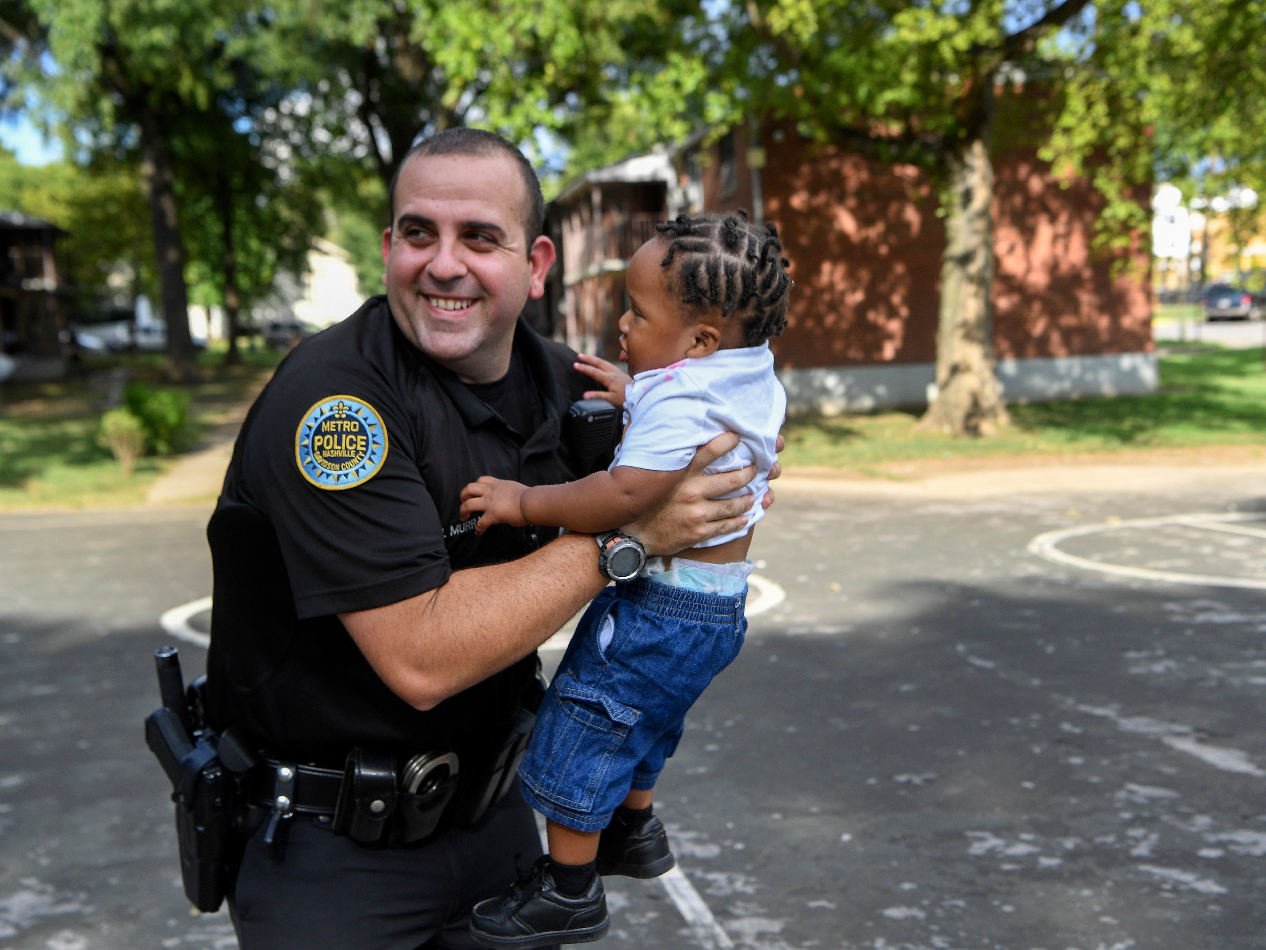 Officer Josh Murray with the Metro Nashville Police Department picks up Eamon Perry, 16 months old, as officers make their rounds through the James A. Cayce Homes housing development Aug. 30, 2018.