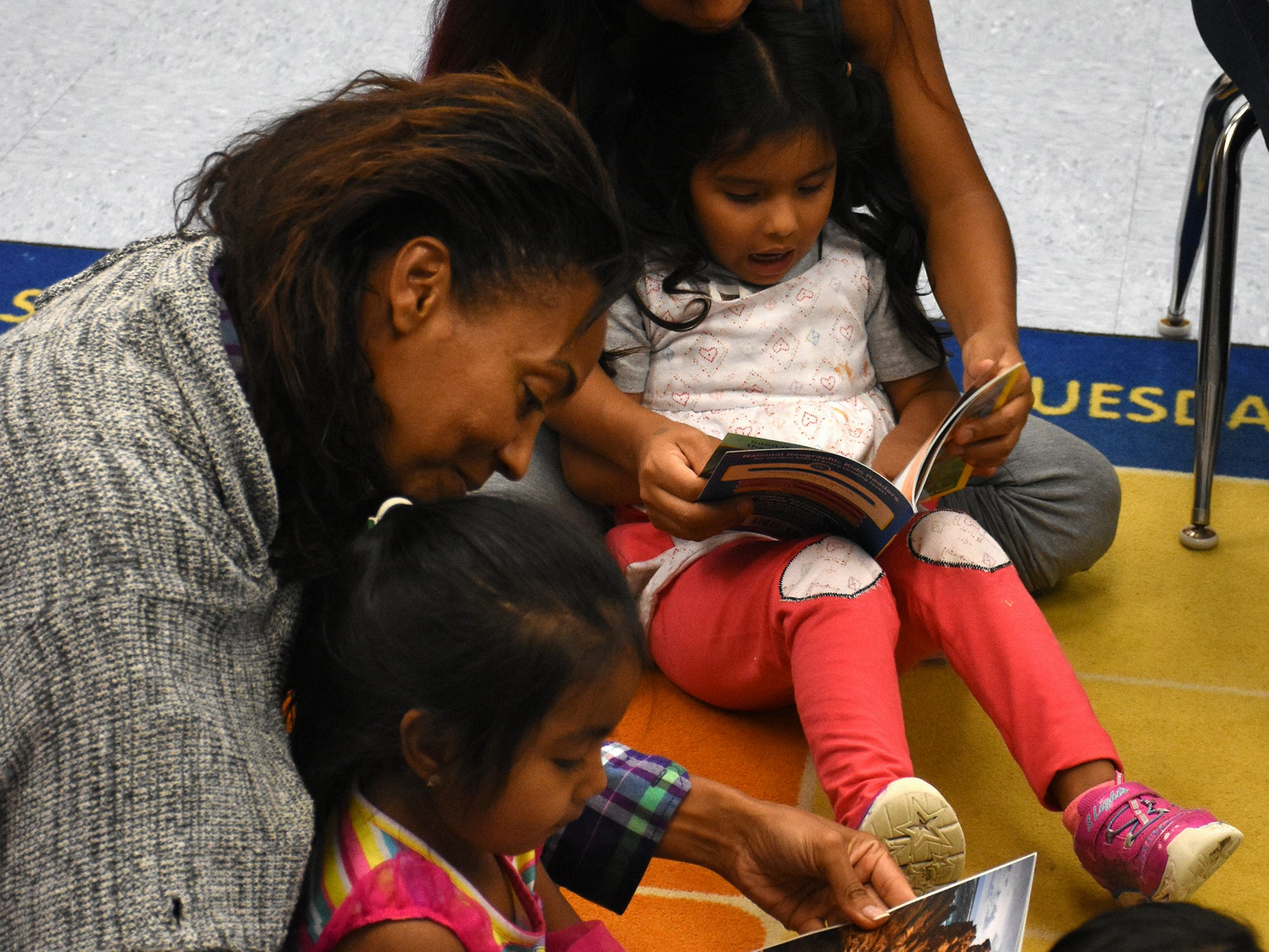 """Volunteers and mothers read with students from """"At the Beach,"""" caught up in the words and pictures. Volunteers conduct """"Children and Parents Reading Together"""" programs with pre-K students in elementary schools through the Literacy Volunteers of Collier County."""
