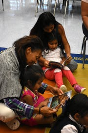 "Volunteers and mothers read with students from ""At the Beach,"" caught up in the words and pictures. Volunteers conduct ""Children and Parents Reading Together"" programs with pre-K students in elementary schools through the Literacy Volunteers of Collier County."