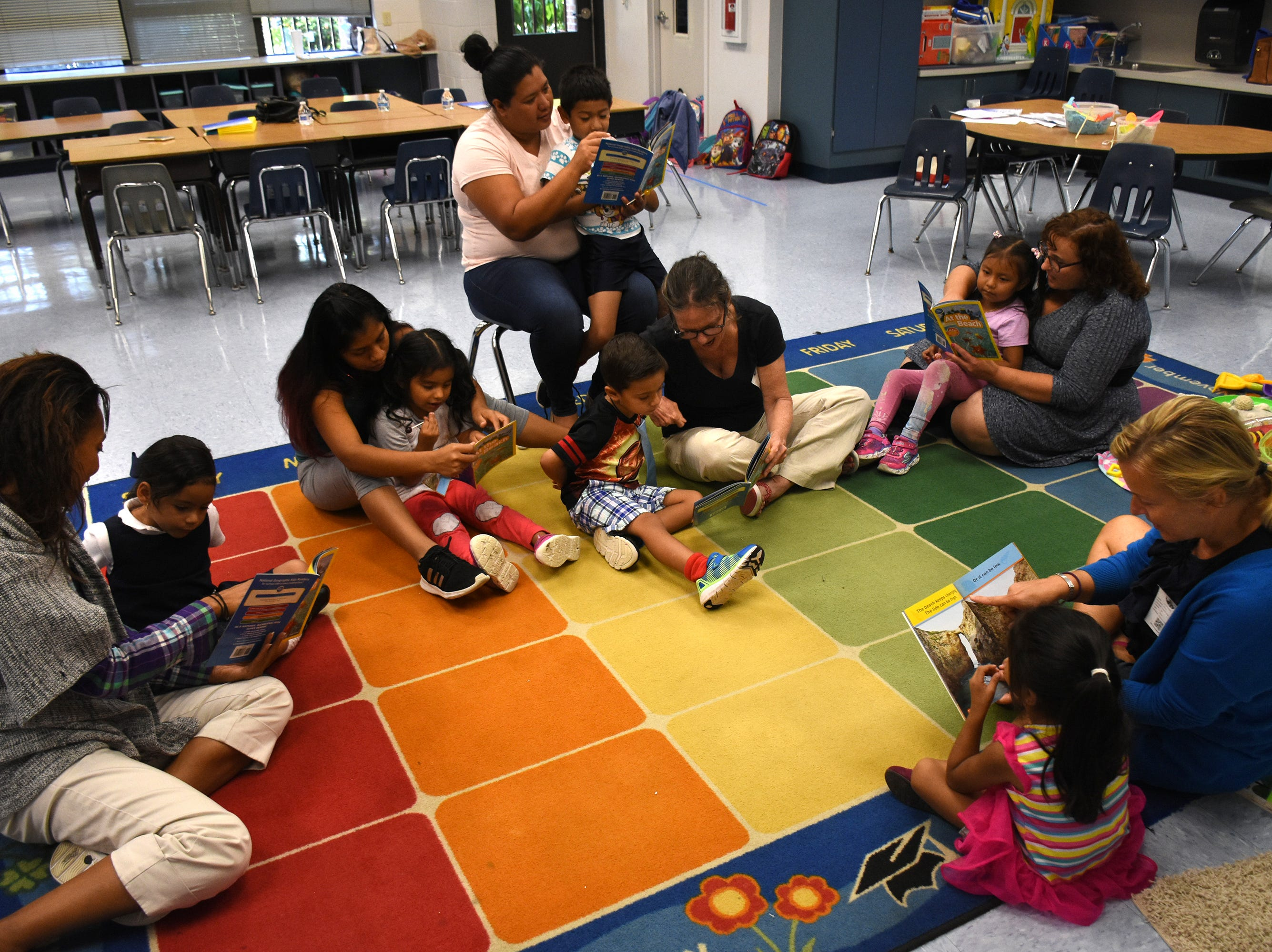 "Volunteer teacher Beata Koperdowski reads to students from ""At the Beach,"" with parents and volunteers following along. Volunteers conduct ""Children and Parents Reading Together"" programs with pre-K students in elementary schools through the Literacy Volunteers of Collier County."
