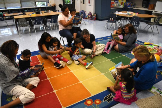 """Volunteer teacher Beata Koperdowski reads to students from """"At the Beach,"""" with parents and volunteers following along. Volunteers conduct """"Children and Parents Reading Together"""" programs with pre-K students in elementary schools through the Literacy Volunteers of Collier County."""