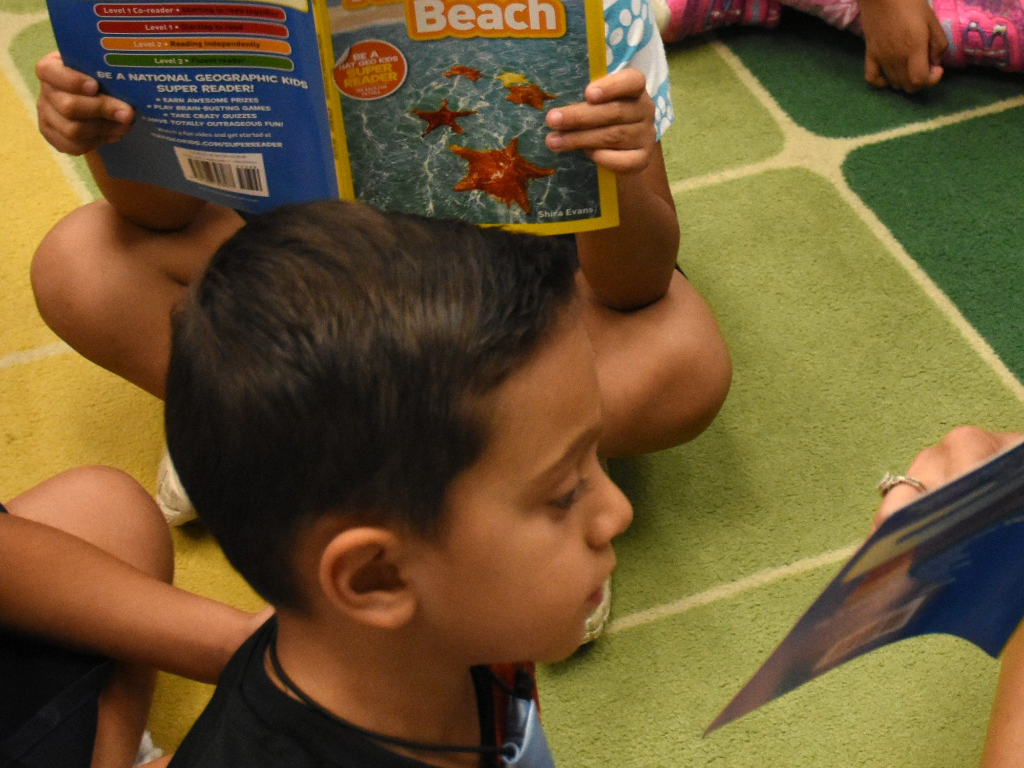 "Jose Perez gets caught up in his reading. Volunteers conduct ""Children and Parents Reading Together"" programs with pre-K students in elementary schools through the Literacy Volunteers of Collier County."