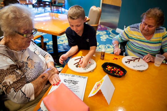 Ryan Hunter, 7, a first grader from Naples Christian Academy, helps Ann Rellas, left, and Jean Damman, right, with an art project during an art buddies program on Thursday, November 1, 2018, at Vi at Bentley Village's Skilled Nursing facility in Naples.