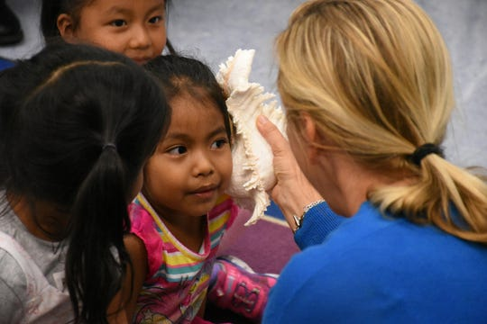 """Volunteer teacher Beata Koperdowski lets a student """"hear the sea"""" in a conch shell as part of a lesson """"At the Beach.""""  Volunteers conduct """"Children and Parents Reading Together"""" programs with pre-K students in elementary schools through the Literacy Volunteers of Collier County."""