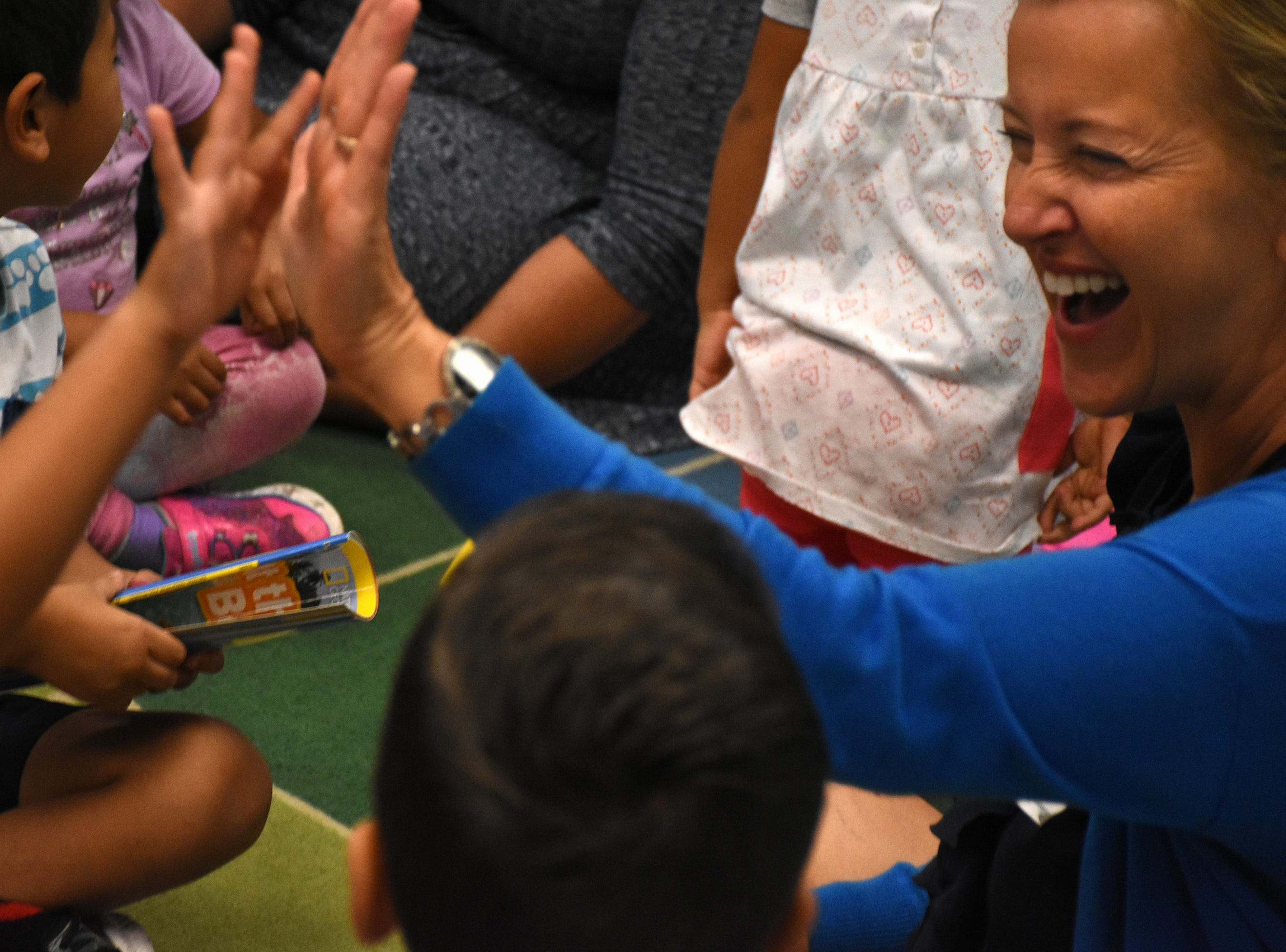 "Volunteer teacher Beata Koperdowski gives high fives to reward right answers and keep the energy level up. Volunteers conduct ""Children and Parents Reading Together"" programs with pre-K students in elementary schools through the Literacy Volunteers of Collier County."