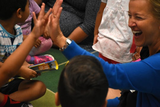"""Volunteer teacher Beata Koperdowski gives high fives to reward right answers and keep the energy level up. Volunteers conduct """"Children and Parents Reading Together"""" programs with pre-K students in elementary schools through the Literacy Volunteers of Collier County."""