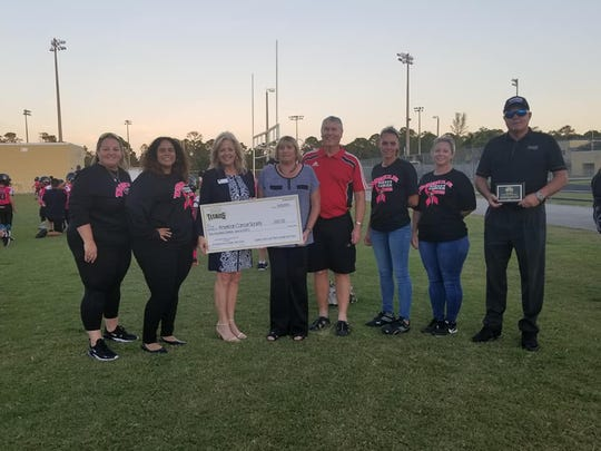 The Golden Gate Youth Titans donated a $500 check to the American Cancer Society after the youth football organization exceeded its fundraising goals.