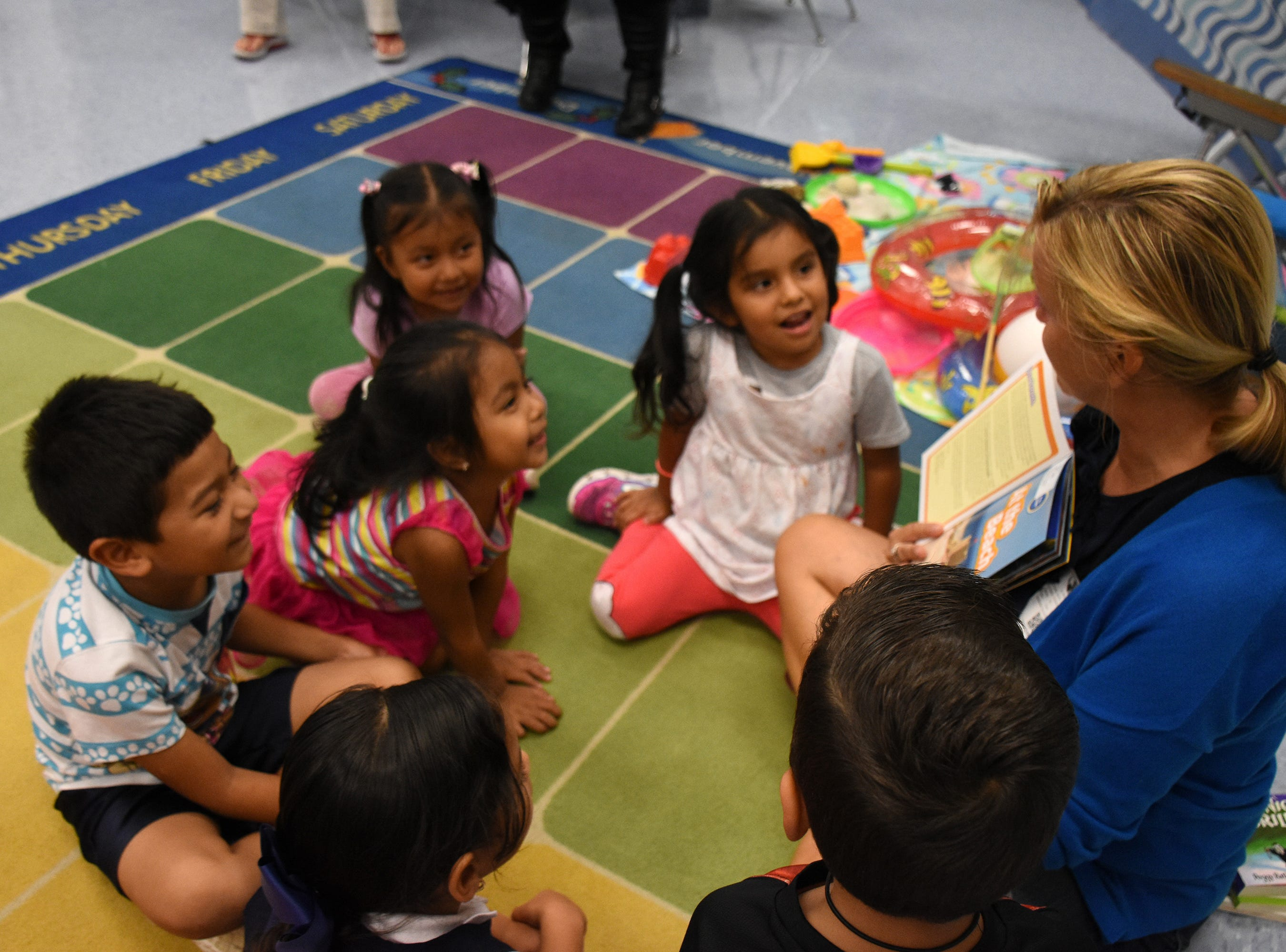 "Volunteer teacher Beata Koperdowski reads to students from ""At the Beach,"" much to their delight. Volunteers conduct ""Children and Parents Reading Together"" programs with pre-K students in elementary schools through the Literacy Volunteers of Collier County."