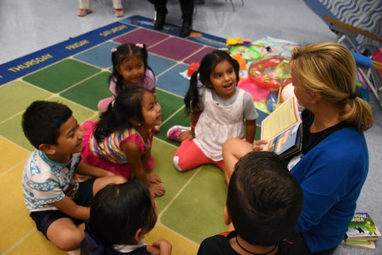 """Volunteer teacher Beata Koperdowski reads to students from """"At the Beach,"""" much to their delight. Volunteers conduct """"Children and Parents Reading Together"""" programs with pre-K students in elementary schools through the Literacy Volunteers of Collier County."""