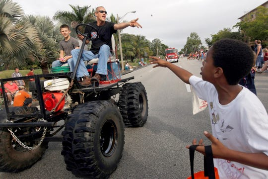 Robert Cottage, center, of Naples, drives his homemade swamp buggy in the 2011 Swamp Buggy Parade on U.S. 41 in Naples. Casey Marshall, left, 10, of Naples, is the passenger, and Zachary Johnson, 9, of Naples, is catching candy tossed by Cottage.