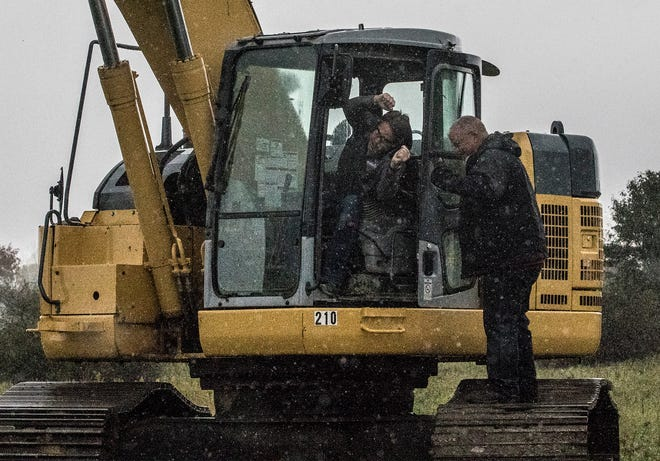 Andy Joseph, president and CEO of Apeks Supercritical, in Johnstown, cheers as he leans out of the track hoe he used to dig the first hole for the expansion of Apeks, which includes an Ohio Grown Therapies' medical marijuana processing facility.