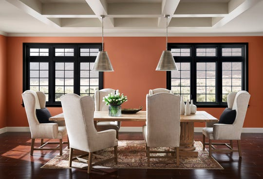 The creme-colored ceiling and furniture fabric, and the ambient light in this dining room, brighten the terra cotta tone of the deep, rich Cavern Clay painted walls.