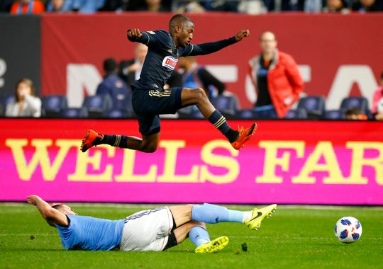 New York City FC defender Maxime Chanot, bottom, plays the ball against Philadelphia Union forward Fafa Picault during the first half of an MLS playoff soccer match Wednesday, Oct. 31, 2018, in New York. (AP Photo/Noah K. Murray)