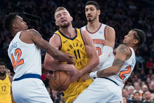 New York Knicks forward Lance Thomas (42), center Enes Kanter (00) and guard Trey Burke (23) defend against Indiana Pacers forward Domantas Sabonis (11) during the first half of an NBA basketball game Wednesday, Oct. 31, 2018, at Madison Square Garden in New York.
