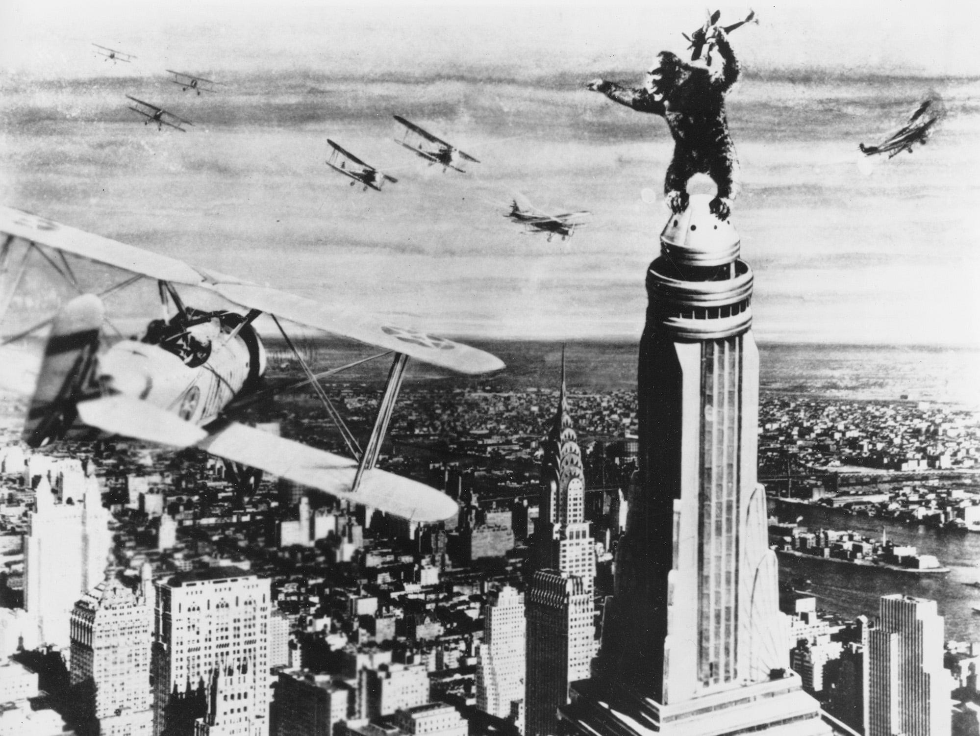 """King Kong stands atop New York's Empire State Building as he holds an airplane during an attack by fighter planes in a scene from the 1933 film """"King Kong.""""  (AP Photo)"""