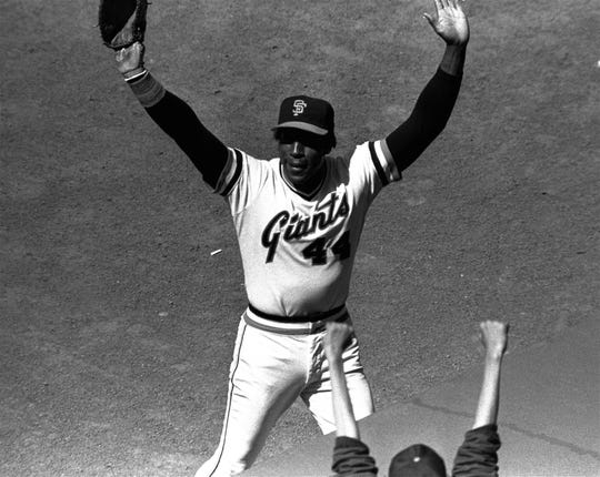 """FILE - In this July 3, 1980, file photo, San Francisco Giants' Willie McCovey raises his hands in salute to the cheering crowd after he was replaced in the lineup in the team's baseball game with the Cincinnati Reds in San Francisco. It was the last home appearance before retirement for the popular veteran.  McCovey, the sweet-swinging Hall of Famer nicknamed """"Stretch"""" for his 6-foot-4 height and those long arms, has died. He was 80.  The San Francisco Giants announced his death, saying the fearsome hitter passed """"peacefully"""" Wednesday afternoon, Oct. 31, 2018, """"after losing his battle with ongoing health issues."""""""
