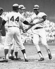 """FILE - In this July 23, 1969, file photo, National League's Willie McCovey of San Francisco is congratulated on crossing home in the third inning of the baseball All-Star Game in Washington after hitting in Hank Aaron (44) in Washington. McCovey hit another home in the next inning. Also shaking his hand is Ron Santo, on deck. McCovey, the sweet-swinging Hall of Famer nicknamed """"Stretch"""" for his 6-foot-4 height and those long arms, has died. He was 80.  The San Francisco Giants announced his death, saying the fearsome hitter passed """"peacefully"""" Wednesday afternoon, Oct. 31, 2018, """"after losing his battle with ongoing health issues."""""""