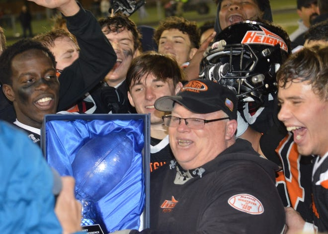 Hasbrouck Heights coach Nick Delcalzo holding the NJIC Tournament trophy with his players surrounding him after the Aviators captured the title in the Oct. 26 contest at Depken Field.