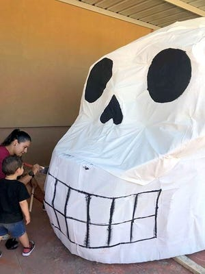 "Monica Topham and her son paint the outlines of a giant skull nicknamed ""Rosa."""