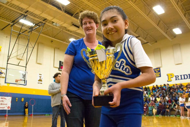 Seventh-grade student Kloie Griffiths presents a trophy for the winning team after the quidditch match at Picacho Middle School during the Unified Champion School banner presentation.