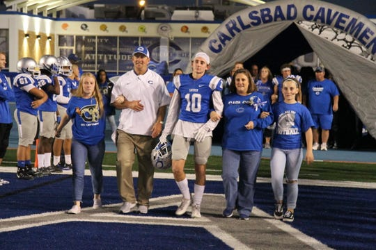 Carlsbad senior defensive back Shawn Bradley (10) is accompanied to the field on Senior night by his family including his father and head coach, Gary Bradley.