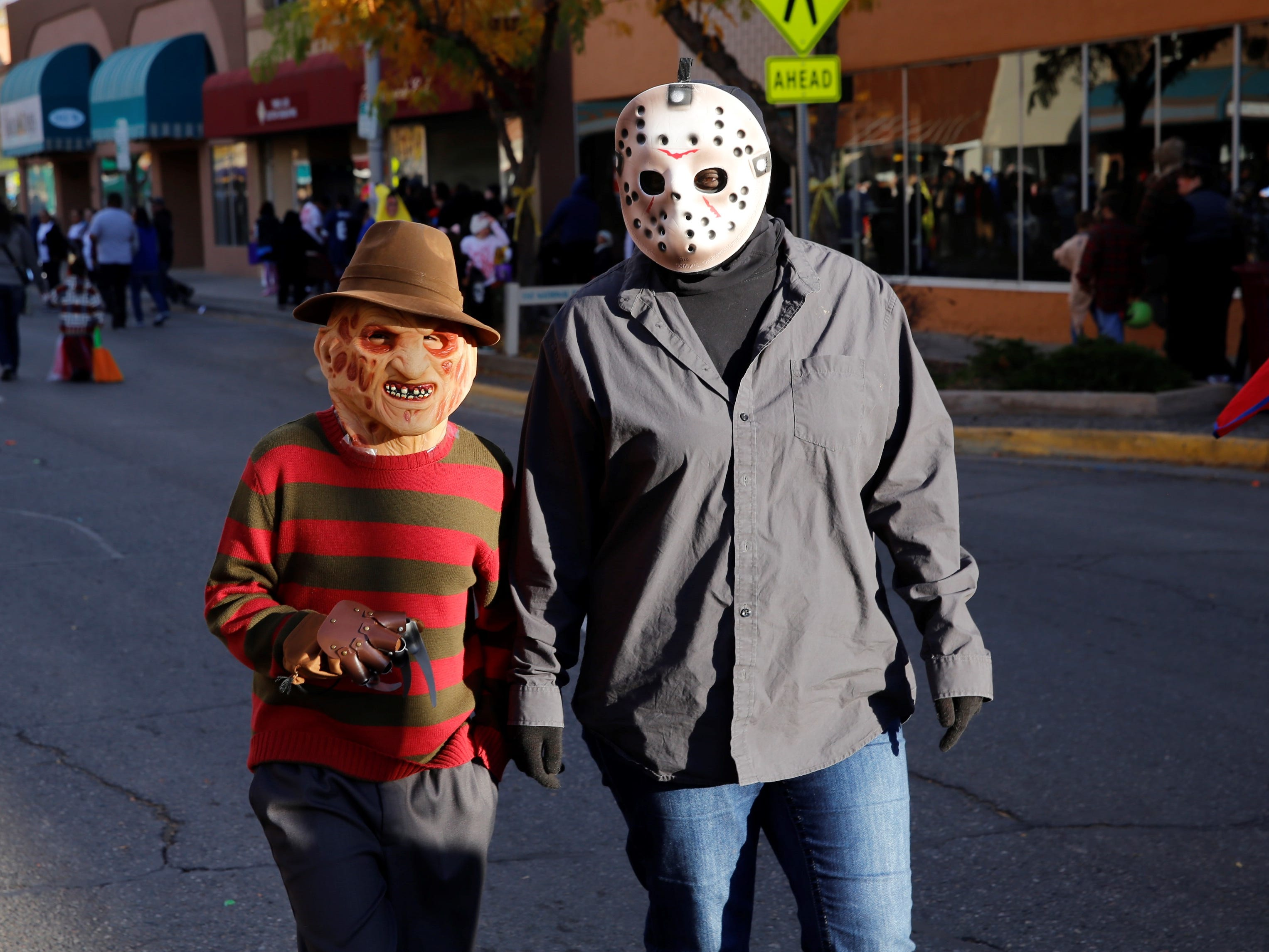 "Santiago Gonzales, dressed as Freddy Krueger from ""A Nightmare on Elm Street,"" and Ursula Begay, dressed as Jason Voorhees from ""Friday of the 13th,"" walk down Main Street during PooPalooza Wednesday in Farmington."