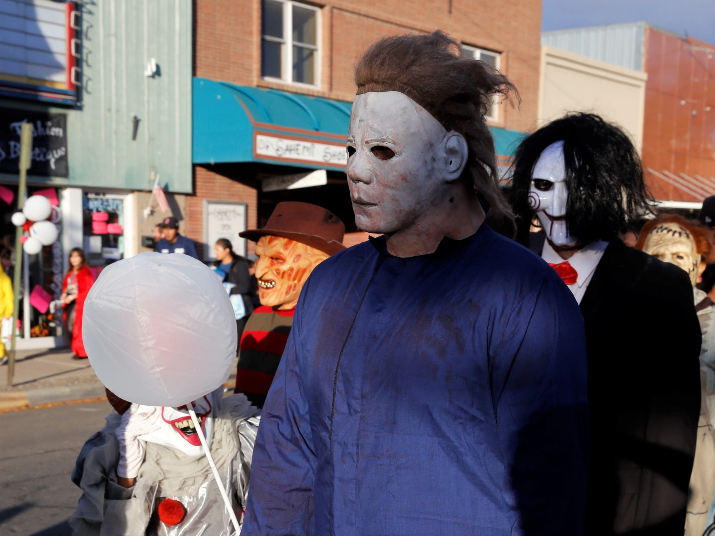 "Corey Blackwater, dressed as Michael Myers from ""Halloween,"" waits in line for candy on Main Street during PooPalooza Wednesday in Farmington."